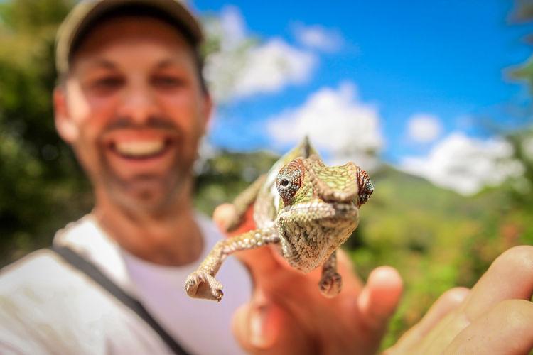 Smiling man holding chameleon