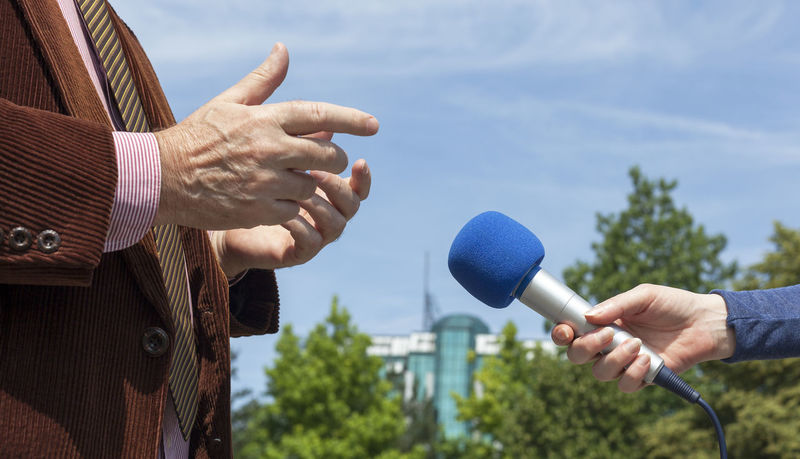 Journalist hand holding a microphone conducting an TV od radio interview Adult Broadcasting Businessman Close-up Communication Conference Day Holding Holding Hands Human Hand Interview Journalist Media Microphone Only Men Outdoors People Politician Press Sky Spokesman Suit