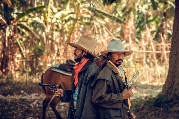 Men holding gun wearing hat standing with horse at forest