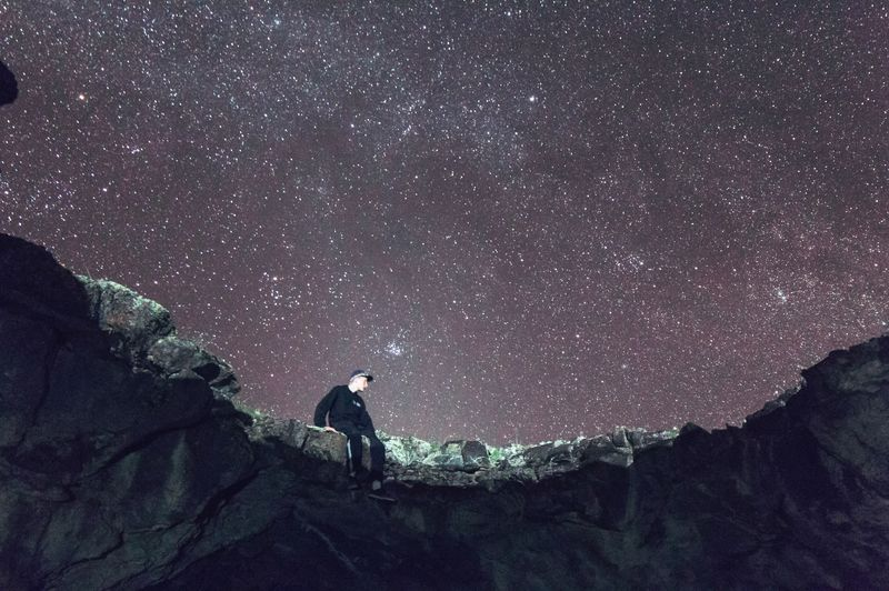 Young Man Sitting On Rocky Mountain Against Stars Filled Sky