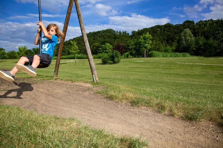 Boy Sitting On Zip Line At Playground