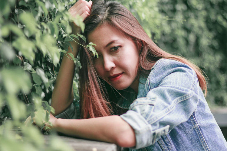 Portrait of beautiful young woman in plant