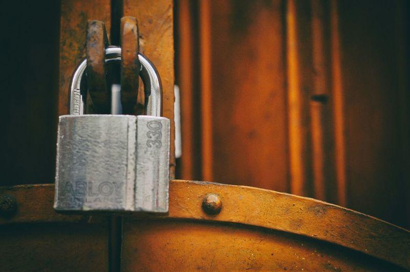 Cropped Image Of Silver Padlock On Metal Gate