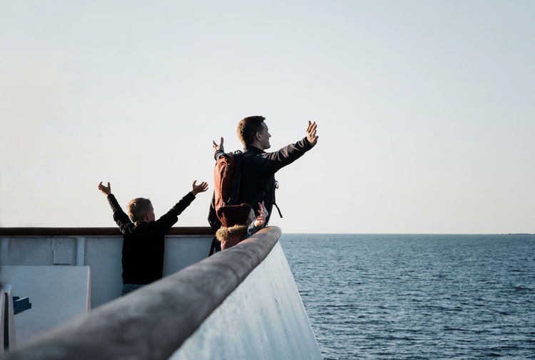 Low angle view of people at sea against clear sky