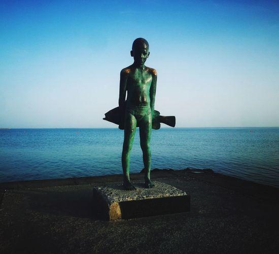 Statue on beach against sky