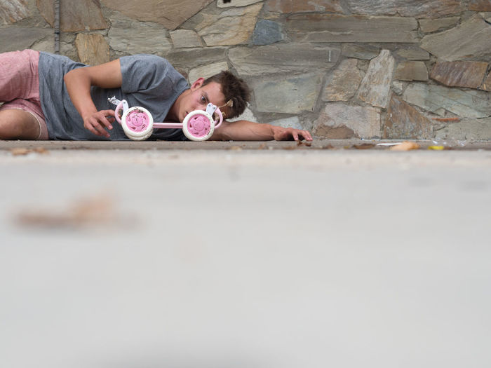 Portrait Of Young Depressed Man With Toy Lying On Footpath