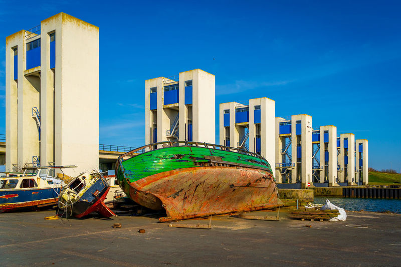 Abandoned boats moored on beach against clear blue sky
