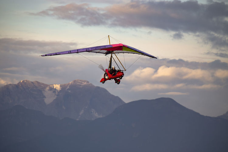 Man flying glider against mountains