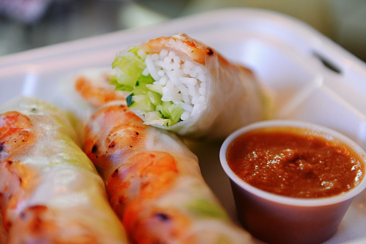 Close-up of spring rolls with sauce in tray