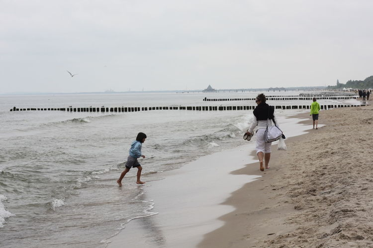 Children playing on beach against sky