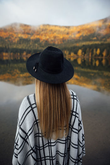 Rear view of woman wearing hat standing by lake