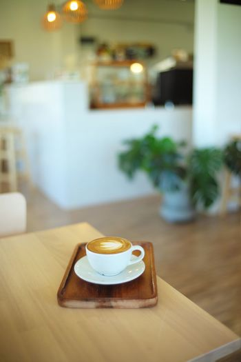 Cup of latte art Coffee in coffee shop Latte Art Table Food And Drink Focus On Foreground Drink Food Cup Indoors  Coffee Coffee - Drink Wood - Material No People Cafe Restaurant Business Domestic Room Freshness Mug Plate Home Interior Hot Drink