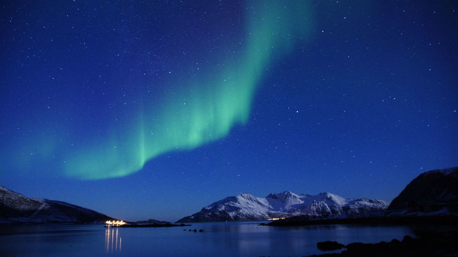 Scenic view of lake and mountains against sky at night during aurora borealis