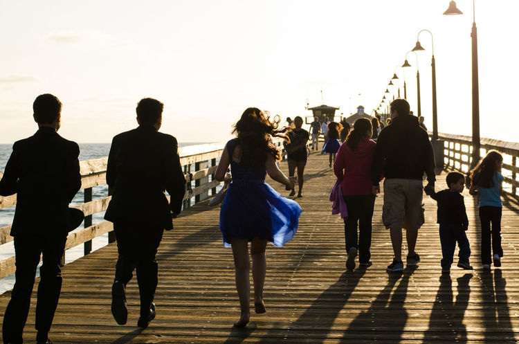 15 year old girl celebrating with some boys in tuxedos on a pier Boardwalk Casual Clothing Clear Sky Footpath Large Group Of People Leisure Activity Lifestyles Men Ocean Person Pier Quinceañera Silhouette Silhouettes Sky The Way Forward Young People Young People Having Fun