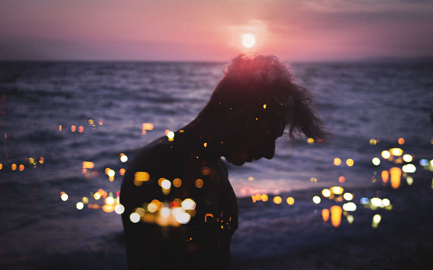 Double exposure image of silhouette man at beach and illuminated cityscape