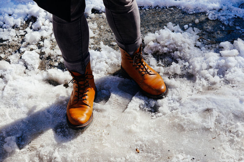 Close up of the legs of a man standing in the snow