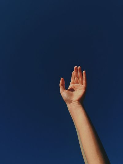Cropped hand against clear blue sky