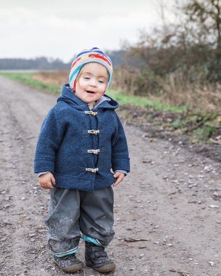 Toddler girl on footpath – Kempen, Germany Adventure Baby Babyhood Boot Cardigan Casual Caucasian Cheerful Child Childhood Coat Communication Curiosity Cute Dirt Duffle Exploring Field First Steps Footpath Front View Full Length Germany Girl Gravel Happy Hiking Innocence Jacket Joy Knit Hat Messy Mouth Mud Nature One Open Outdoors Pants People Portrait Road Rural Standing Sweater Talking Toddler  Walking Winter Wool One Person Leisure Activity Real People Day Clothing Casual Clothing Lifestyles Focus On Foreground Warm Clothing Males