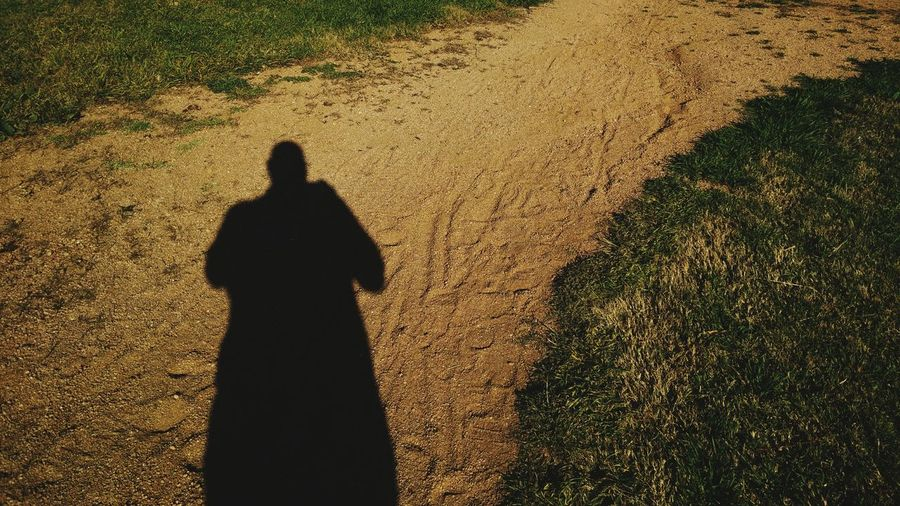 Shadow Of Man Standing On Field