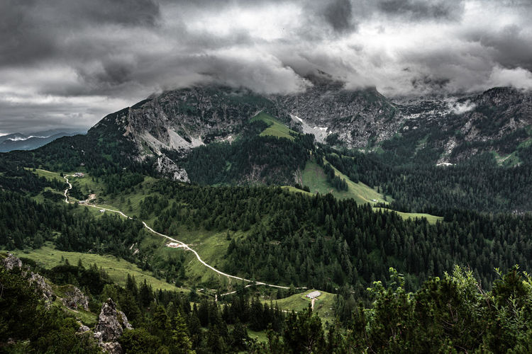 Scenic view of mountains against sky with dark clouds
