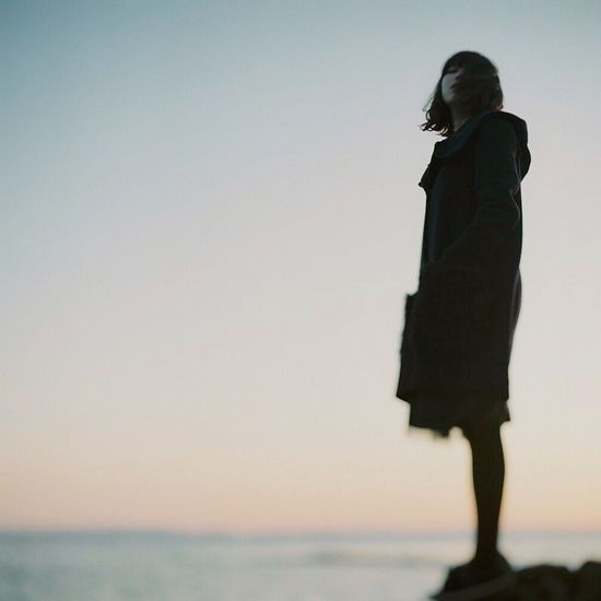 Woman standing by sea against clear sky