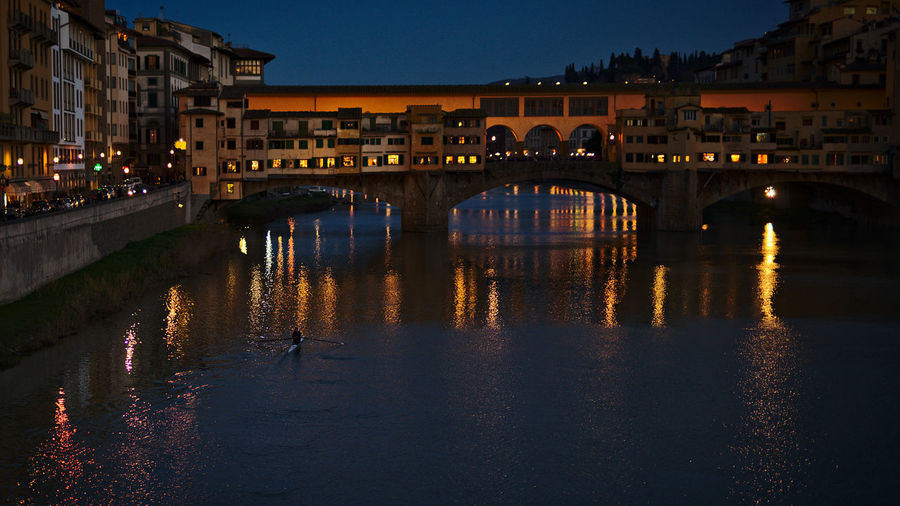 Illuminated bridge over river by buildings against sky at dusk