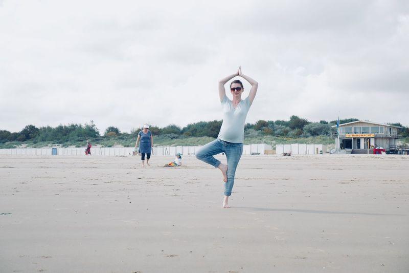 Full Length Of Woman Performing Yoga At Beach Against Sky