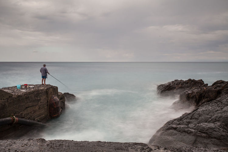 Man fishing at sea shore against cloudy sky