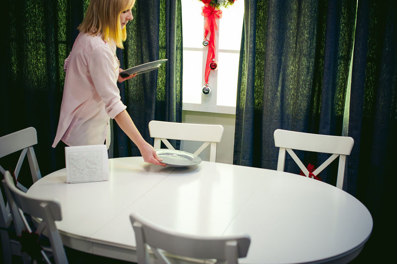 Young woman setting table at home