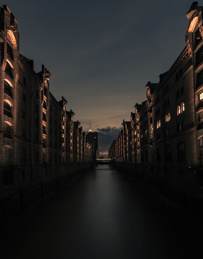 Canal amidst buildings against sky at night