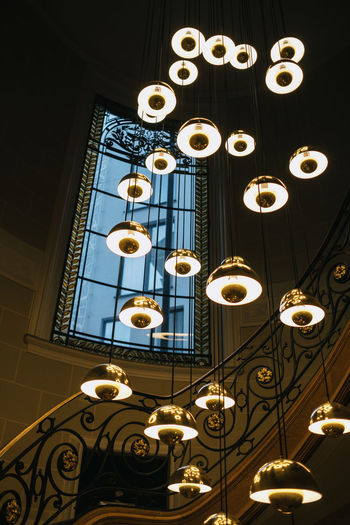 Low angle view of illuminated pendant lights hanging on ceiling in building