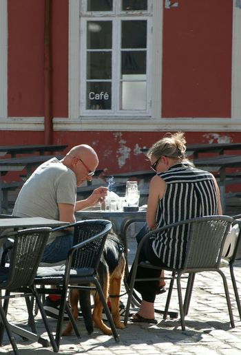 People sitting on table by building