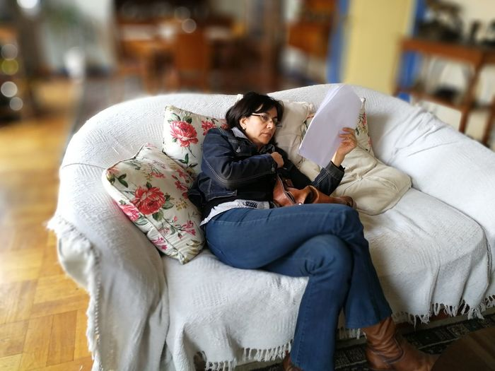 High angle view of woman reading document while lying on sofa at home