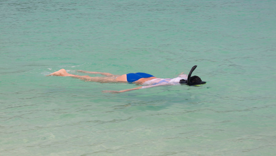 High angle view of person lying in sea