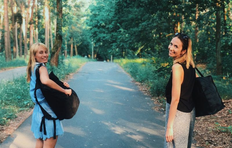 Two young woman walking Tree Females Women Plant Lifestyles Leisure Activity Two People Looking At Camera Outdoors Nature Girls Togetherness Real People Road Day Casual Clothing