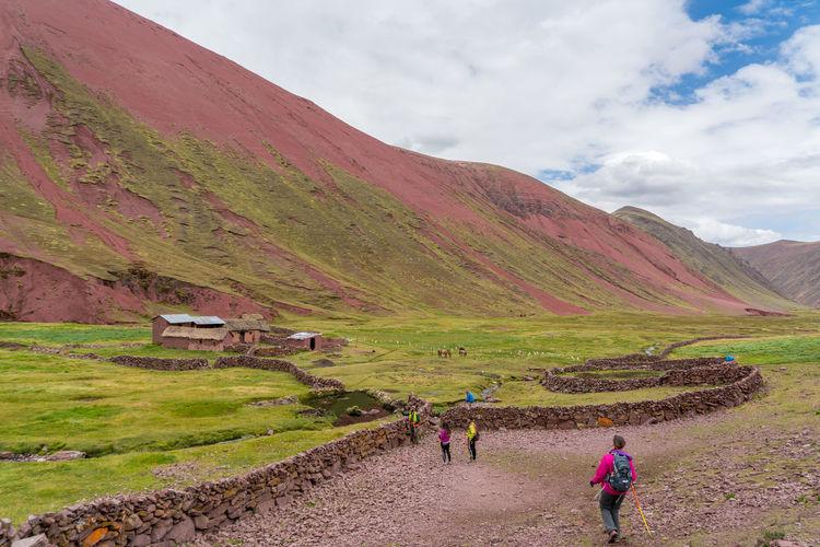 People walking on field by mountain against sky
