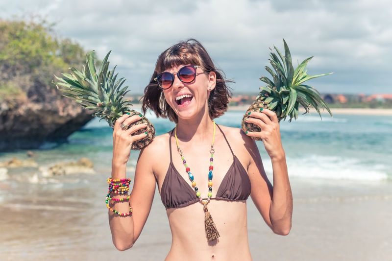 Happy young woman holding pineapples at beach against sky
