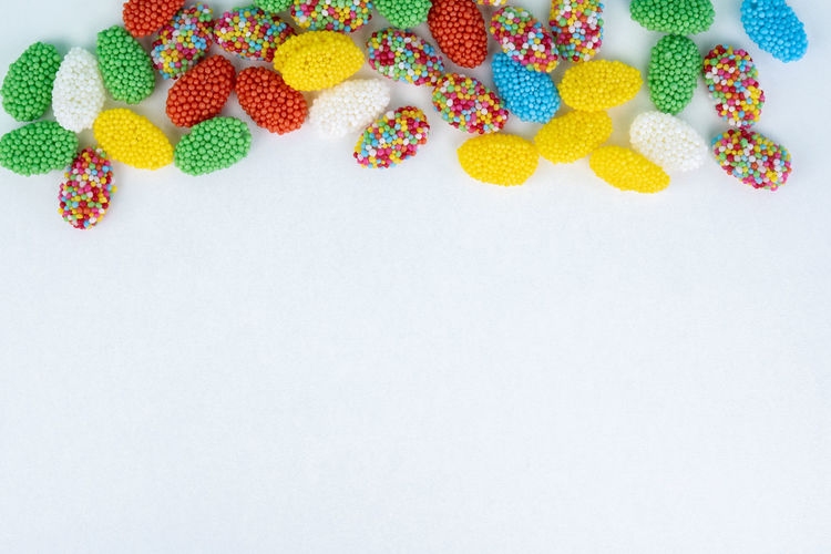 colored candy on a white background White Background Multi Colored Still Life Copy Space Studio Shot Indoors  Sweet Food High Angle View Sweet No People Indulgence Food Food And Drink Creativity Close-up Large Group Of Objects Unhealthy Eating Candy Variation Temptation Wallpaper Easter Celebration