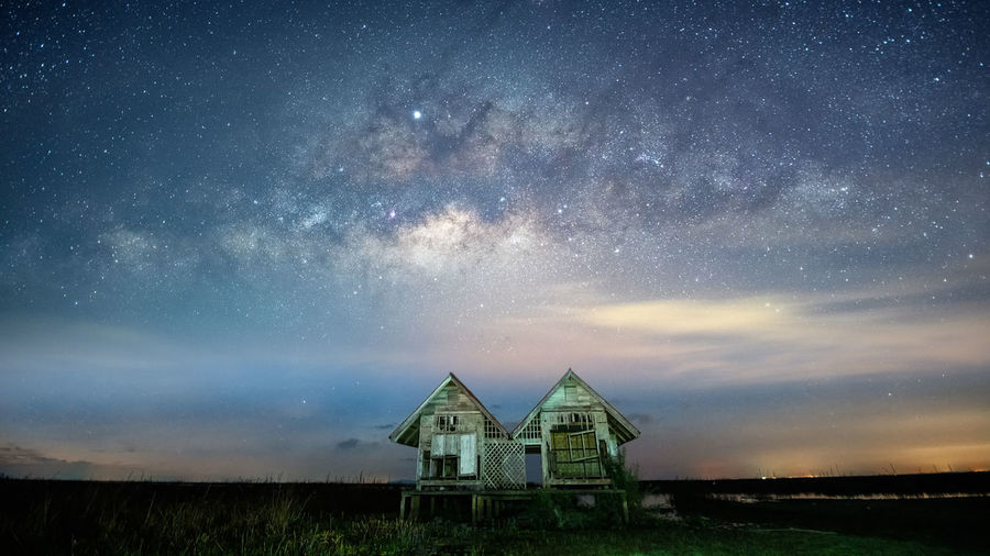 Low angle view of abandoned huts against star field in sky at night