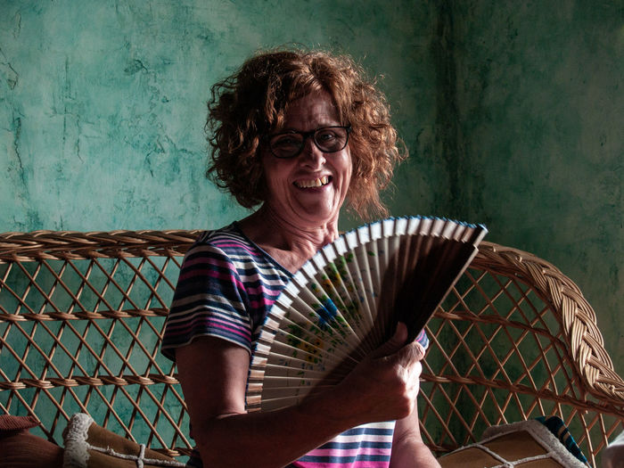 Portrait of smiling woman holding hand fan at home