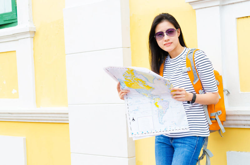 Portrait of woman holding map while standing against building