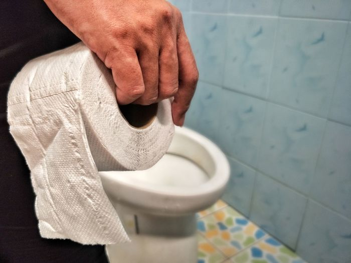 Midsection Of Man Holding Toilet Paper In Bathroom