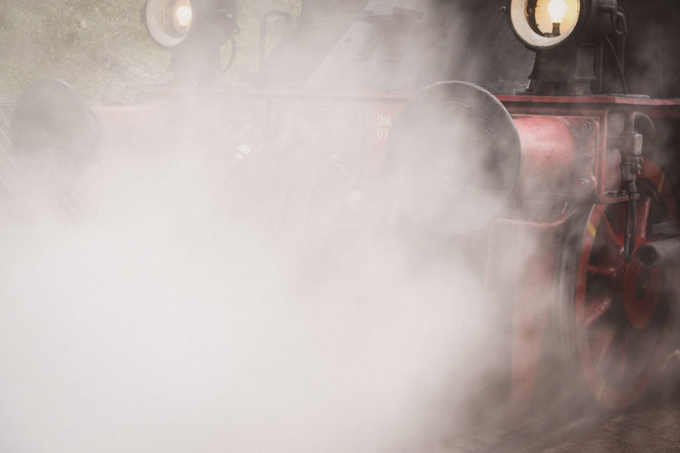 Close-up of steam engine with steam