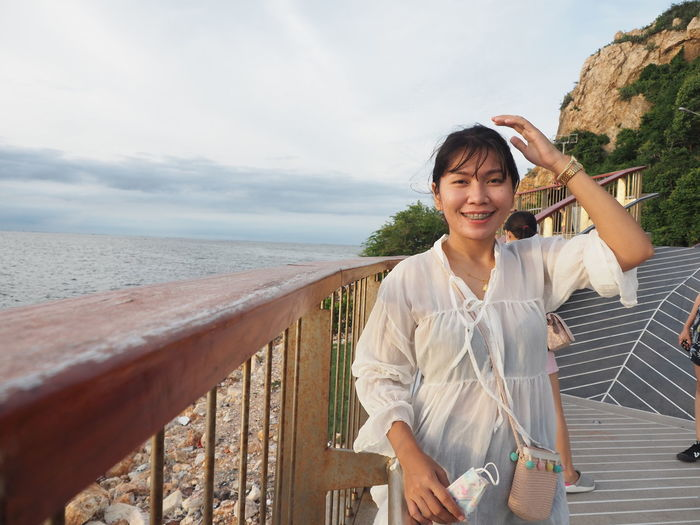 Portrait of smiling woman standing on railing against sea