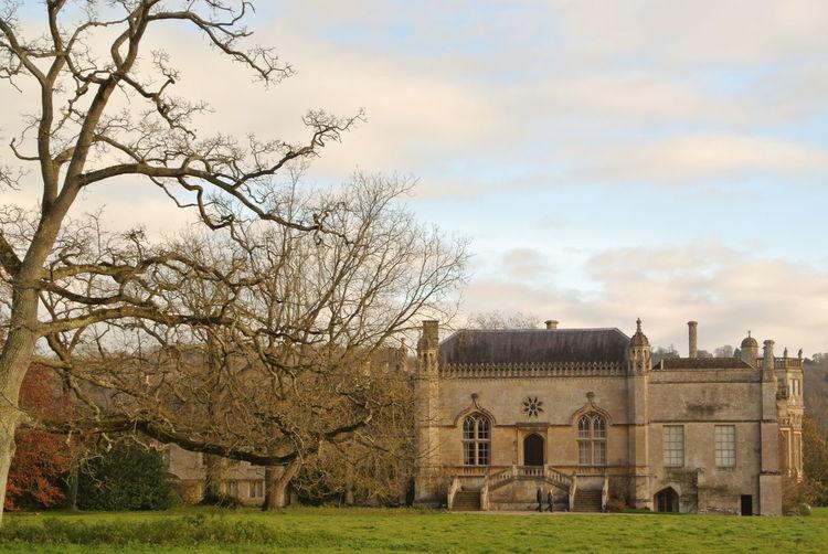 Lacock abbey on field against sky