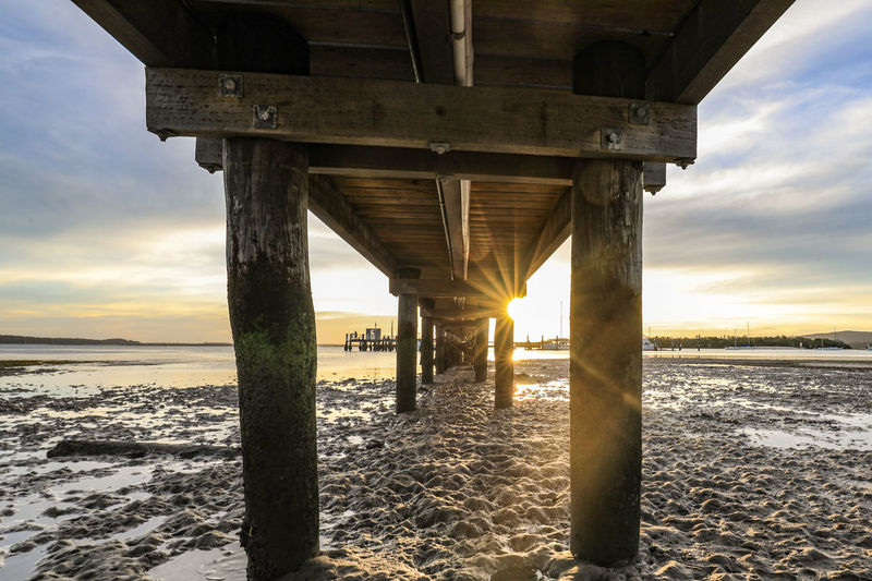 Timber jetty leading to sun setting over ocean at low tide Sky Sunset Water Land Sea Beach Nature Built Structure Sun Scenics - Nature Architecture Beauty In Nature Cloud - Sky Sunlight Pier Tranquility Tranquil Scene No People Connection Horizon Over Water Architectural Column Underneath Outdoors Australia Australian Landscape Nature Sunrise Rising Setting Evening Morning Dawn Dusk Day Outdoor