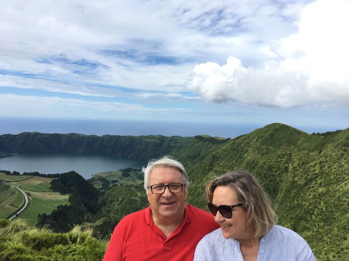 Smiling couple on mountain against sky