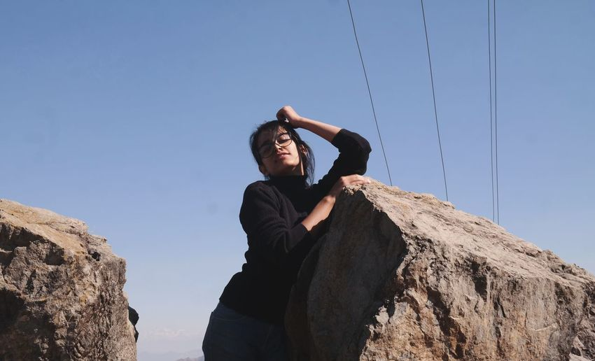 Low angle portrait of young woman standing on rock against clear sky