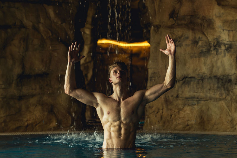 Shirtless muscular man with arms raised in swimming pool against illuminated lighting equipment