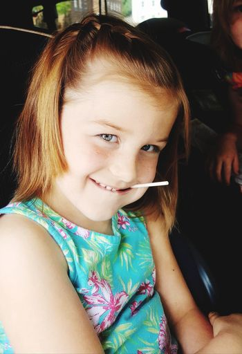 Portrait Of Smiling Girl Eating Candy